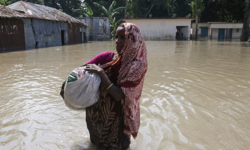 A woman walks in floodwaters as she holds a sac following heavy monsoon rains